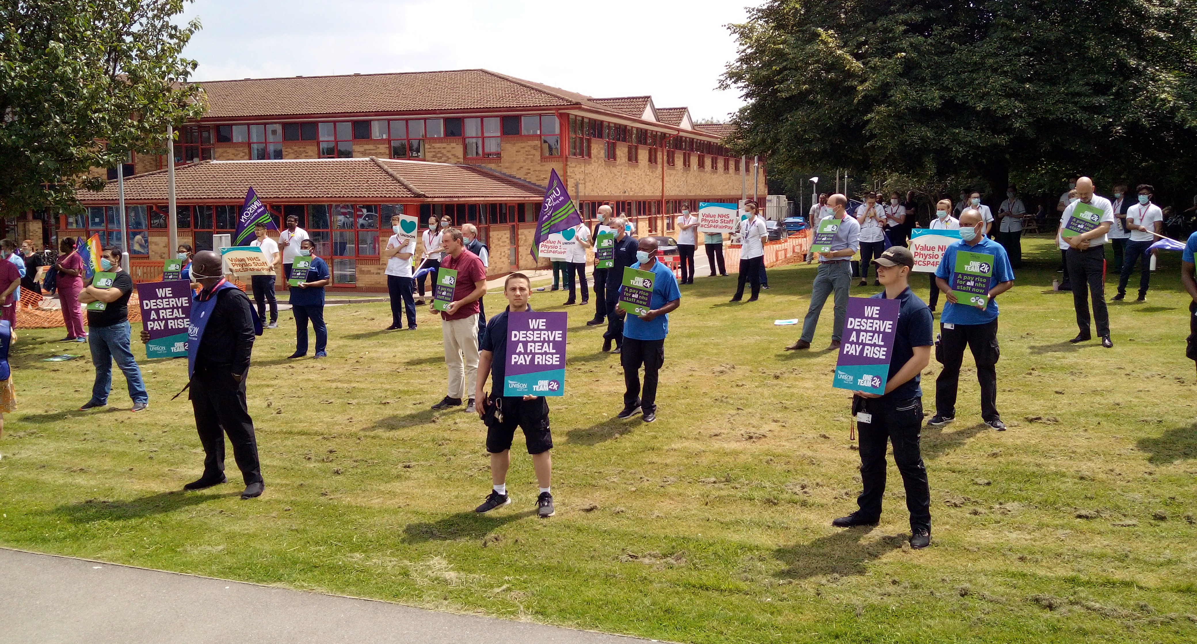 image of a large group of NHS staff standing outside taking part in a pay campaign activity. They are socially distanced so standing far apart from each other