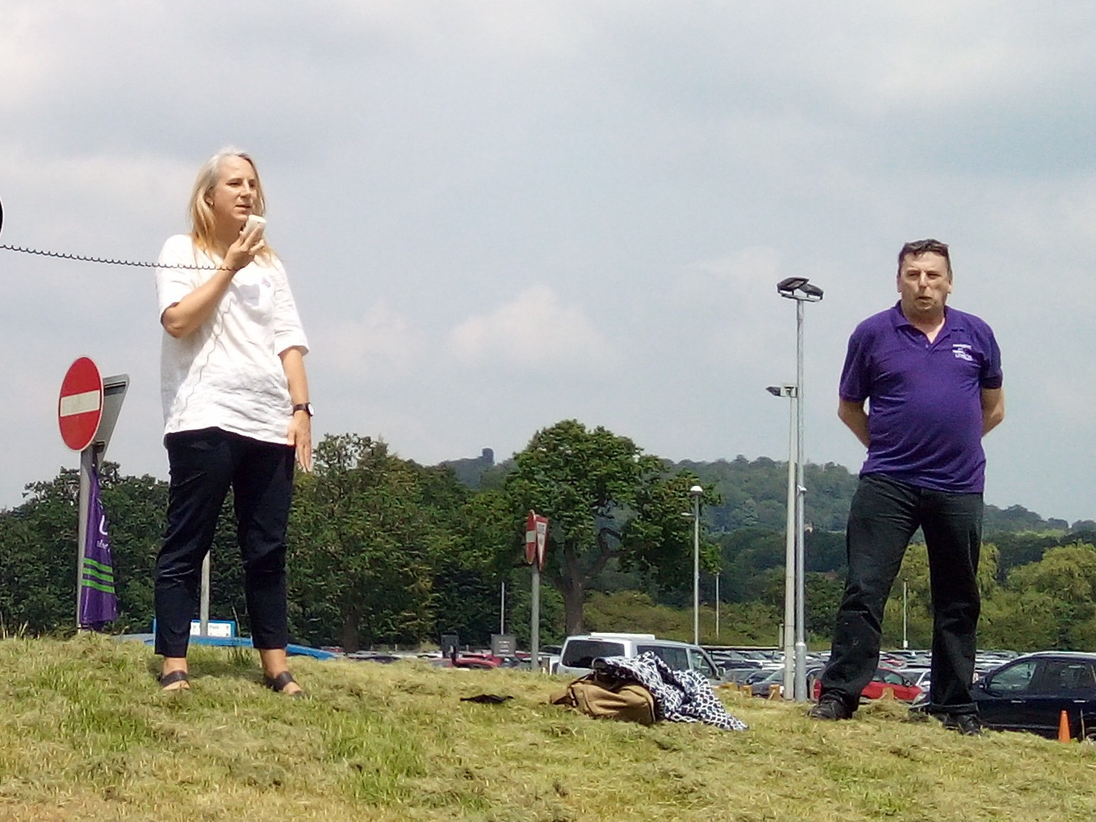 Image of Sarah Gorton, UNISON head of health, speaking at an outdoor rally. She is accompanied by a UNISON organiser wearing a purple polo shirt