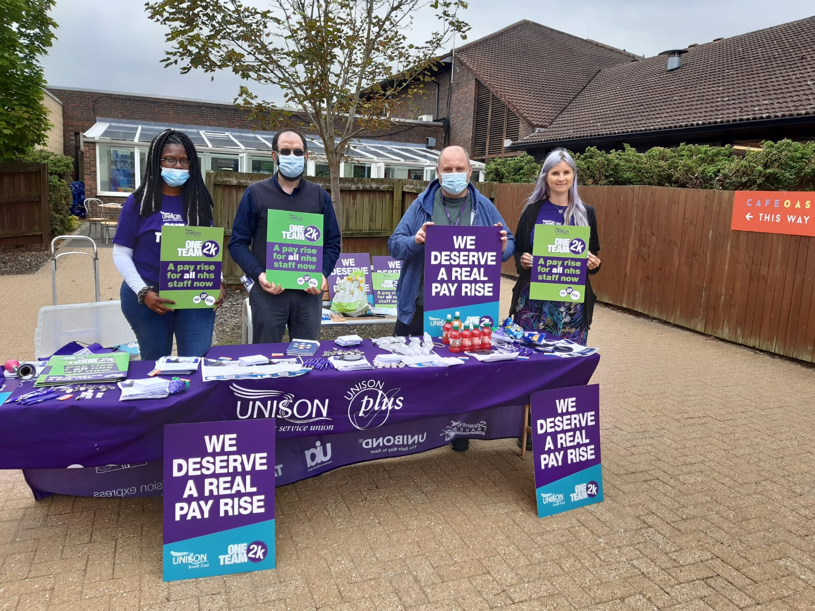 image shows four UNISON activists standing behind a table, they are holding placards asking for a pay rise for NHS staff