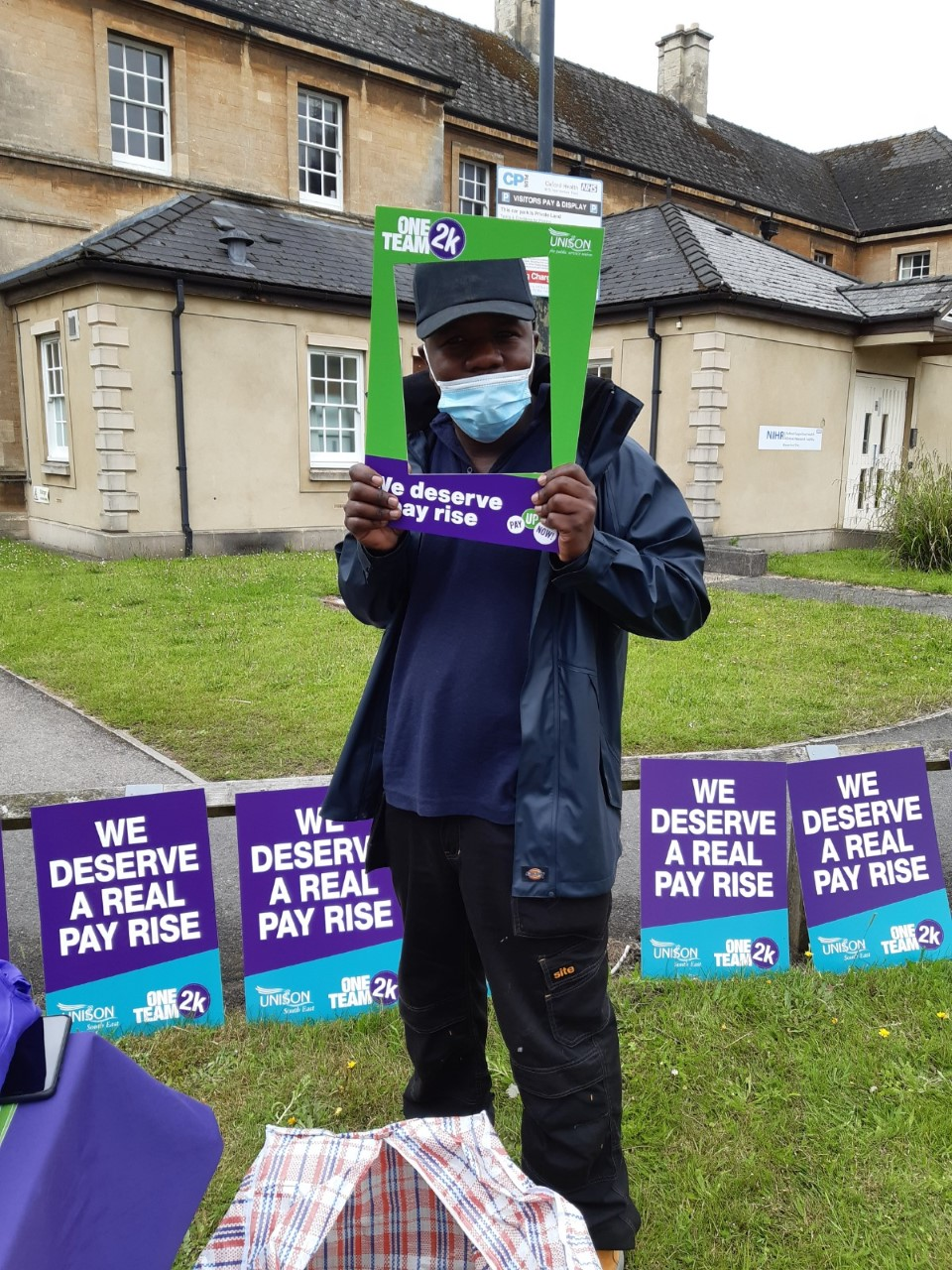 image of a member of NHS staff standing outside a hopsital building. They are holding a banner that frames their face, that says 'we deserve a pay rise' In the background there are more banners that say 'We deserve a real pay rise'